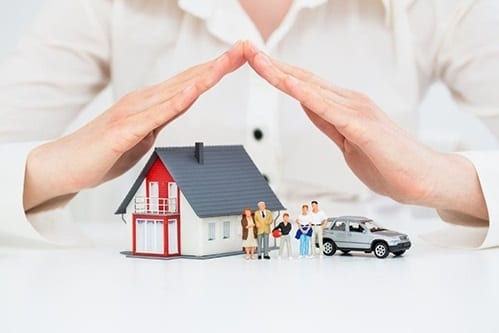 A Person holding their hands over a toy house and family - as if they were protecting them
