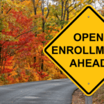 """an image of a road sign that says """"open enrollment ahead."""" The sign is just before a curve in the road. There is beautiful fall foliage all around."""
