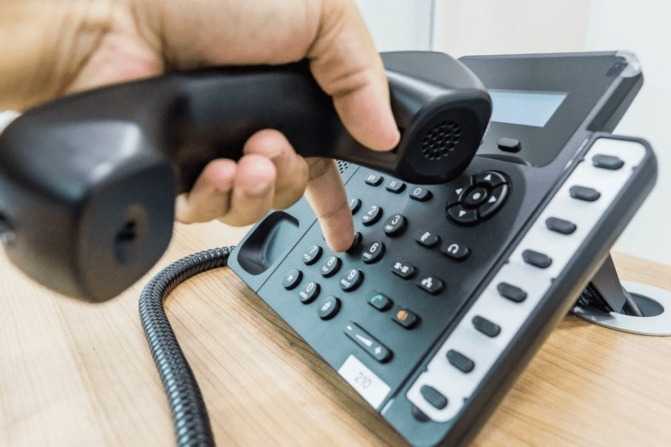 An image of a phone on a desk with a hand dialing numbers.