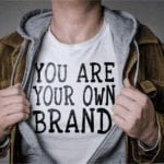 """an image of a man showing you his t-shirt. the t-shirt says """"you are your own brand."""""""